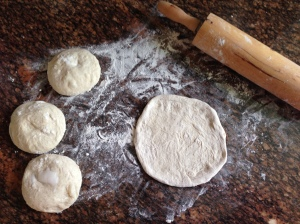 Rolling out the dough balls on a floured countertop